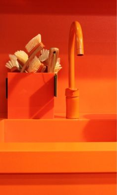 A photograph of an awesome bright orange kitchen sink and faucet.