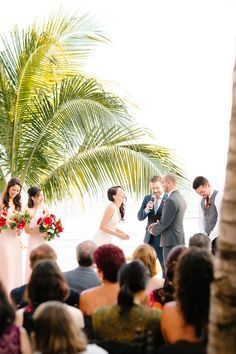 Bold wildflower bouquets lend a bright red pop to the elegant seaside ceremony.