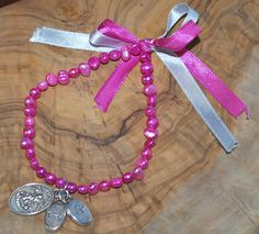 Bracelet rose avec trois brelogues; trust (confiance), wish (vœu), St. Michael et  archet.  Elastique pour s'adapter à tous les poignets.