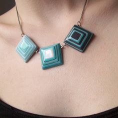 Kristin Kemper of The Spaces in Between makes original necklace pendants by combining dozens of layers of acid-free colored paper. She sands and seals the layers, forming perfectly smooth, solid shapes. They're lightweight, but durable. And pretty!