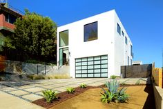 Clean lines and simplicity make this home a modern day case study. Every room frames the view of the downtown Los Angeles Skyline. Photography by Eric Charles #modern #contemporary #glassgaragedoor #droughttolerentlandscape