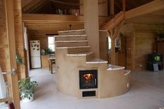 The design concept of the rocket mass heater takes the heat of the flames and runs it along through a mass of cob that heats and retains the heat to slowly dissipate it into the home. Labor Junction / Home Improvement / House Projects / Heating / Green Homes / Stairway / Fireplace / House Remodels / www.laborjunction.com