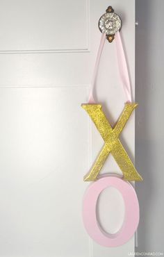 Cupid's Corner: DIY XO Door Hanger    Here's what you will need:    cardboard 'X' and 'O' (available at most craft stores)  pink and gold acrylic paint  paintbrush  pink satin ribbon  hot glue gun