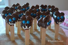 chocolate covered marshmallow teddy bear pops for baby shower food, mini M&M's for face, Hershey's Chocolate Drops for ears, stuck into burlap covered styrofoam.