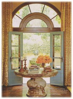 Blue doors.  always have loved a round foyer table...beautiful with arched double doors