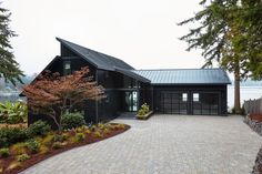 A new exterior painted black with updated driveway and landscaping creates a bold front yard that sets the tone for HGTV Dream Home 2018, a moody modern escape with a coastal twist.