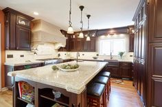 The dark traditional #cabinets paired with light #countertops, stone hood and tumbled marble #backsplash gives this #kitchen it's old world feel. #TraditionalKitchen #MyKitchen #DreamKitchens