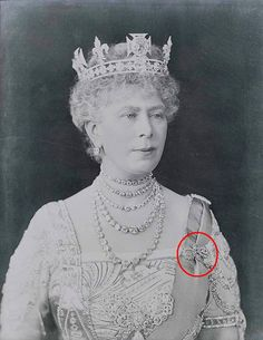 HM Queen Mary wearing her crown (without arches), diamond stud earrings, five diamond collet necklaces, Queen Adelaide's brooch surrounded by the two sides of the Cockade brooch, her diamond bar brooch on her shouder, and a brooch (circled in red) now most certainly converted into a pair of earrings by her grand daughter Queen Elizabeth II (you can see them here: http://www.pinterest.com/pin/541909767636730422/ ).