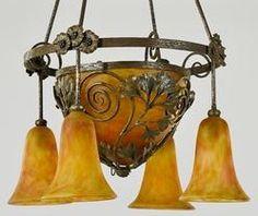 """Frères DAUM & Edgar BRANDT (1880-1960), suspension """"Ginkgo Biloba et Anémones"""" à quatre lumières en chute et une profonde vasque centrale. Monture en fer forgé patiné, les motifs floraux dans la cage recevant l'obus et en ceinture. Les tulipes et la vasque centrale en verre marmoréen orange, jaune et rose. La monture signée du cachet E. BRANDT sur le cerclage, chaque verrerie signée DAUM Nancy à la Croix de Lorraine. Hauteur : 94 cm. Diamètre : 54 cm."""