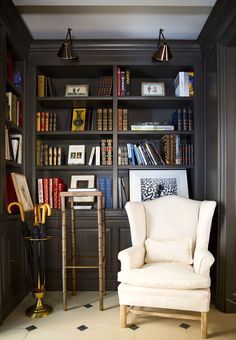 Cozy reading corner with built-in library shelves, brass wall sconces and a cozy wingback armchair.
