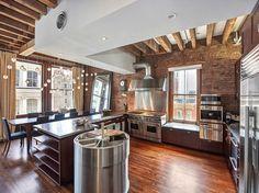 plafond en bois à la française, mur de brique exposée et appareils électroménagers en acier inox dans la cuisine style industriel