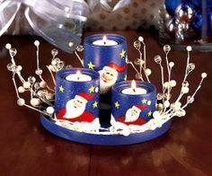 """5-Pc. Santa Votive Candleholder Set by ABC Distributing. $24.99. 8 inch diameter candle holder set. 3 votive candle holders. Metal with Faux berries and twigs. This 5-Pc. Santa Candle holder Set makes a lovely centerpiece. 3 vibrant, hand painted candle holders are perfectly sized for holding your favorite tea lights or votives (candles not included). They are nestled by an attractive wreath and fit in a matching metal tray (8"""" dia.). Large candleholder, 4"""" x 2-5/8"""" dia. ..."""