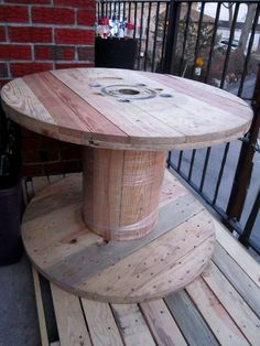 Wooden spool as table! electrical companies have these in spades. If you contact them, they'd probably be happy to get rid of one. They're made of unfinished wood, so you can stain or paint. :o)