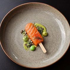 """Salmon lollipop"" - Citrus star anise cured and raw salmon with avocado purée, wasabi aioli, salmon keta, puffed wild rice, wasabi pea granola & dill. A stunning dish uploaded by @piersdawson. Plate by @artistjodidawson & photo by @emmloufen #gastroart"