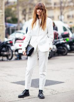 Caroline de Maigret wears a menswear-inspired white suit with black oxfords
