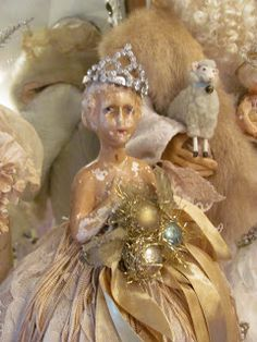 shabby doll adorned with a tiny tiara, tiny vintage Christmas bulbs and silver tinsel....