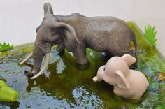 Use gelatin mixed with water to create an African swamp crossed be elephants. Sensory bin ingredients: gelatin, water, rocks, tree branch, foam grass and toy animals.