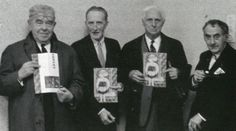 """René Magritte, Marcel Duchamp, Max Ernst, and Man Ray, attending Bill Copley's exhibition at the Stedelijk Museum, line up holding a copy of the exhibition catalogue, in which announces """"Tremendous Deliriums"""", 1966. Ph. Ed van der Elsken"""