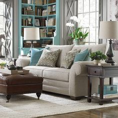 Grey and turquoise living room with wood table.