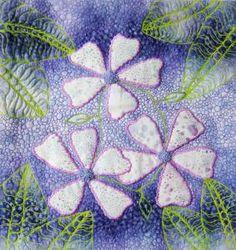 http://www.tafalist.com/members/ruby-wings-designs  Appliqued flowers.  Art quilt by Ruby Wings Designs.