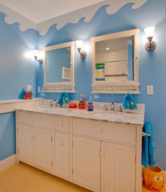 Underwater world theme on the walls with unique cabinets turns this bathroom into a world of fun