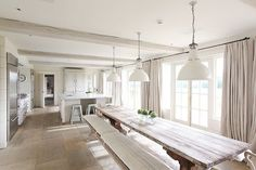 open kitchen with extra long dining room table, bench seating, french doors, floor length curtains, and three pendant lights