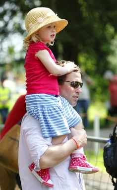 Peter Phillips carries daughter Savannah Phillips on his shoulder as they watch the International Carriage Driving Grand Prix event during day 4 of the Royal Windsor Horse Show at Home Park on May 17, 2014 in Windsor, England.