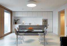 Pavimenti in resina bianca, cucina su misura in total white, più isola in cemento e l'iconico tavolo di Cassina firmato Le Corbusier per il luminoso living di Maison MGD, ristrutturata nel 2012 da Ralph Germann a Montreux, Svizzera