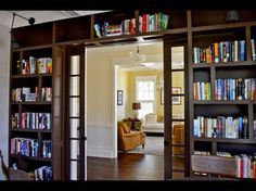 Pocket French doors lead into the library and are surrounded by dark brown built-in bookcases that homeowner Scott Bailey designed. Swing-arm fixtures, ordered through Masterpiece Lighting, shine light on the upper shelves.