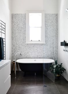 Stand alone black bath tub with stunning grey tile statement wall | Austin Design Associates