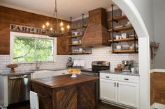 Fixer Upper - Rustic kitchen features creamy white cabinets adorned with oil-rubbed bronze pulls paired with gray quartzite countertops and a white subway tiled backsplash accented with gray grout flanking a stainless steel stove under barn board range hood with wood and plumbing pipe shelves on either side.