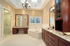 Several wood vanities are present in this bathroom, but the corner tub together with a glass door shower are what really make it special.