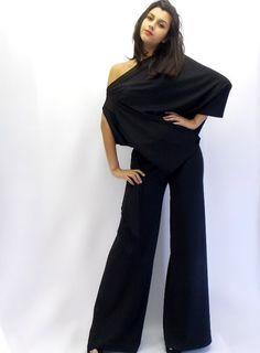 Black jumpsuit made of jersey and chiffon. Asymmetric jumpsuit dress with large pants and asymmetrical top. Jumpsuit is made of two pieces: pants on elastic belt and asymmetrical blouse that is caught sideways hidden staple Black beads lateral sleeve closure. Elegant black jumpsuit. Material: