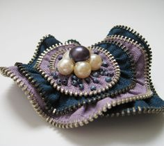 Made from new metal zippers and backed with felt and pin back.    It is accented with a 6 small beads.    Measures approximately 3 X 2.75 inches. Item