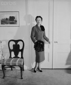 The Duchess of Windsor, who again wins a place in the list of the world's best dressed women, is shown here wearing a blue suit trimmed with fur on one shoulder and carrying a fur-tailed muff.