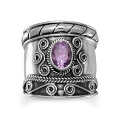 Handmade Oxidized Bali Style Amethyst Ring 83446. This handmade ornate oxidized sterling silver ring has a lined design around one edge and swirls with rope pattern around the other. The center features a 5mm x 7mm oval amethyst with rope edge and swirl design on each side of the stone. The band graduates from 21mm in the front down to 7mm in the back. This ring is available in whole sizes 5-11. .925 Sterling Silver Jewelry Rings