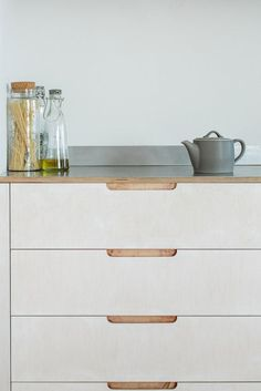 Sustainable Kitchens Eco Kitchen - A close up of the four lye-treated drawer cabinet with routed drawer pulls. Showing off how effortlessly the brushed stainless steel worktop meets the wood.