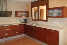 Mobiliario de cocina fabricado en tablero marino, chapado con cerezo, con ranuras horizontales y barnizado. Encimera y frontal de pared con silestone blanco capri.