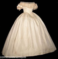 Circa 1862 ivory silk faille two-piece wedding gown, with  a boned and stayed bodice with fashionable deep hem points, and piped at the neckline, armscyes, and waistband. A pleated tulle bertha accented with silk velvet ribbons that repeat on the short sleeves, with a pleated tulle modesty insert above, and a lace up closure at the back. The sweeping skirt has a crinoline lining, with a beautiful double box pleated waistband, a back hook and eye closure, and a turned hem.