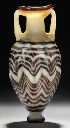 A GREEK CORE-FORMED GLASS AMPHORISKOS   EASTERN MEDITERRANEAN, CIRCA 6TH-5TH CENTURY B.C.   With opaque white ovoid body, cylindrical neck with everted rim, applied aubergine marvered threads wound spirally and tooled into a zigzag pattern, aubergine trail around knob base and rim, twin vertical handles, rim restored  4 1/8 in. (10.5 cm.) high