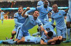 Aguero lies on the turf as his team-mates pile on following the striker's last-minute winn...