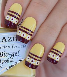 Creative yellow themed French tip nail art. The French tips are painted in black polish as well as thin strips in the middle of the nail. There are also cute little flower designs in black and white polish that add to the charm of the nail art.