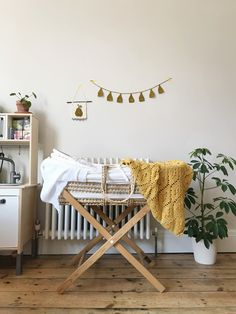 Made with merino wool and cotton blend yarn. This mustard yellow baby blanket adds mid-century cool to your nursery.