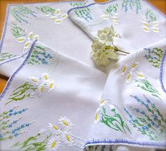 A beautiful, very pretty daisy embroidered linen tablecloth in a lovely coloured hued floral design. Hues of blue, white, yellow and greens with a touch of pale pink, suitable for any interior decor. Ladder stitch edging in blue and lilac, very pretty! Pre Loved good used condition. Embroidered on to a white linen fabric . Approx measurements 31 Inches x 33 Inches All my items listed are Vintage. Pre-Loved Second Hand Treasures will always inevitably show some kind of little evident signs...