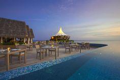 """Todas as quartas-feiras damos a conhecer um hotel com encanto. Esta semana fazemos as malas e apanhamos o avião para longe, muito longe, para abraçarmos o sol e o bom tempo. Rumamos até à ilha de corais de Male, nas Maldivas, para conhecer um luxuoso hotel de cinco estrelas com 75 espetaculares """"villas"""": 45 têm acesso privado à praia e 30 encontram-se mesmo """"em cima"""" do mar."""