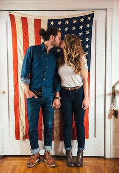 Hipster couple standing in front of American Flag by Trinette Reed Available to license at Stocksy.com