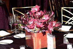 Rich purple hues in a centerpiece are elegant and regal against a deep plum linen.  www.konceptevents.com