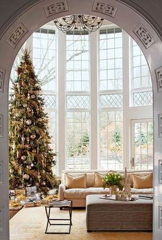 The architecture in this home is incredible with floor to ceiling windows flooded with natural light, and the detailed fretwork in the archway. The Christmas tree is absolutely beautiful.