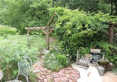 """Using our broken, battered  patio as the basis for this courtyard, we removed  large chunks of the concrete, here and there. We filled in the empty spots  with old brick. We then used the remaining """"chunks"""" to build steps up a slope.It has a pleasant old world look to it. Jeri"""
