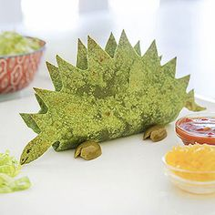 Tacosaurus.   Fold spinach wrap in half and use kitchen shears to cut dino shape (template linked) Unfold and lightly coat one side of the wrap with cooking spray. Refold it (oiled side out) and lay on a baking sheet. Place crumpled pieces aluminum foil inside the wrap to hold the shell open as it bakes. Bake until slightly crisp, 2 to 3 minutes per side (the wrap will harden as it cools). Once it cools, draw a face with a food writer. Add green olive feet as shown and serve with taco…